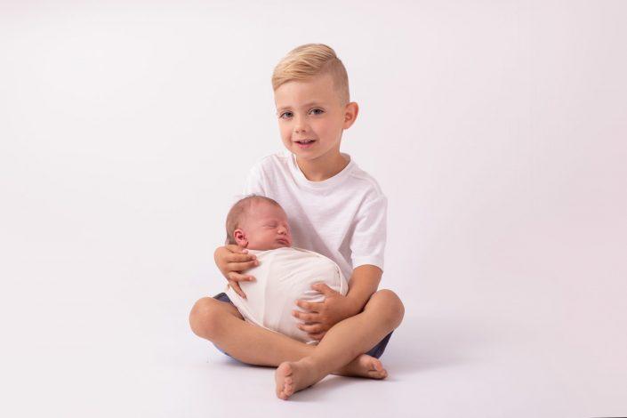 grosser-bruder-haelt-neugeborenes