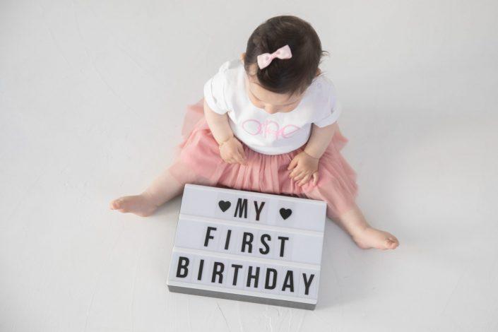 Baby mit Schild erster Geburtstag
