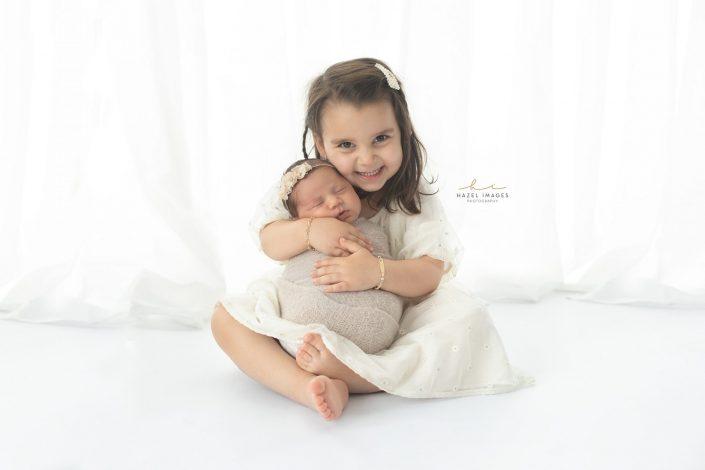 große-schwester-haelt-neugeborenes