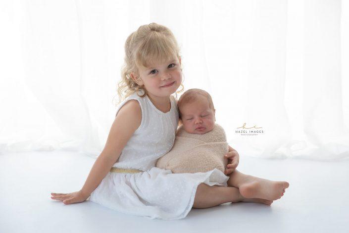 große-schwester-hält-neugeborenes