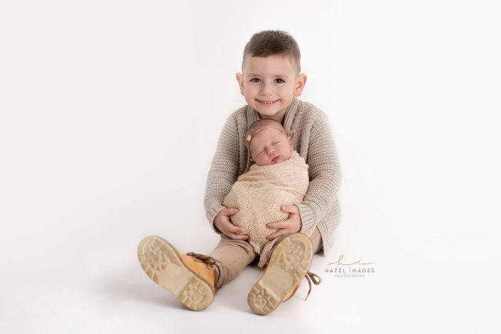 großer-bruder-hält-neugeborenes