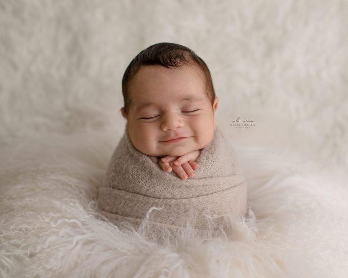 Neugeborenes in Tuch gewickelt lächelnd