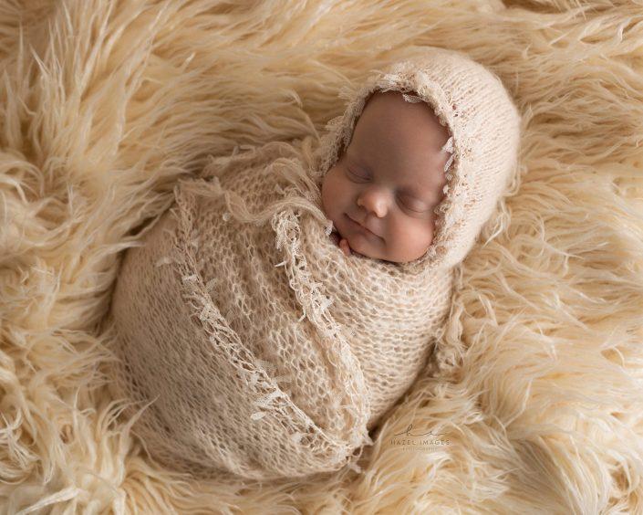 Neugeborenes schlafend in Tuch gewickelt