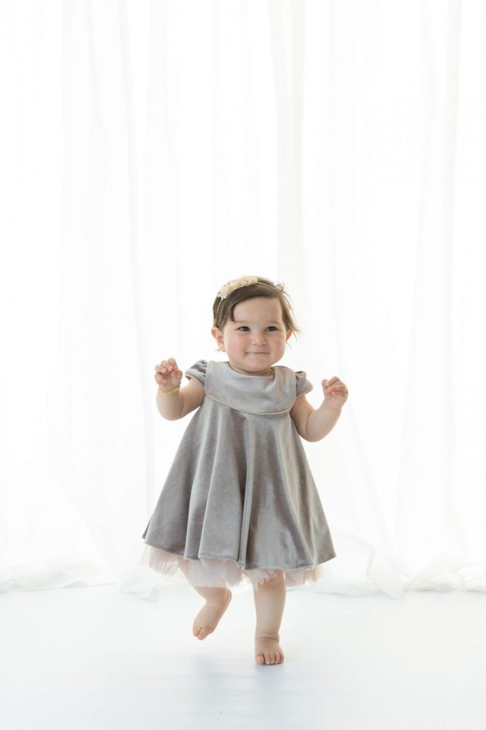 Baby in Kleid laufend